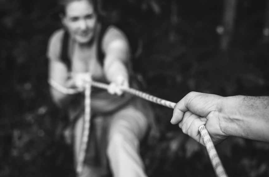grayscale photo of person pulling up woman using rope