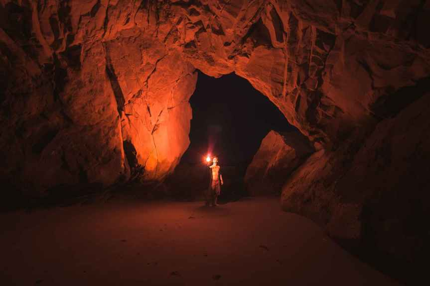 person standing and holding lamp inside cave