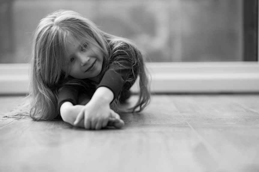 grayscale photo of girl lying on floor